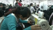 Textile Garment Factory: MS side view of worker in FG with factory BG Workers Stock Footage