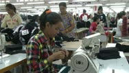 Textile Garment Factory: MS worker at station 1, pan to station 2 Workers Stock Footage