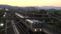 Japanese train rolls into station at dusk Stock Footage