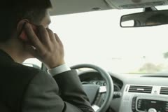 Young handsome man using mobile phone in the car NTSC - stock footage