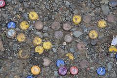 Bottle caps amongst pebbles (HD)c Stock Photos
