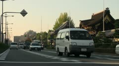 Early morning traffic passes Japanese temple in Kyoto Stock Footage