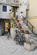 Bicycles under the stony stairs in Fazana Stock Photos
