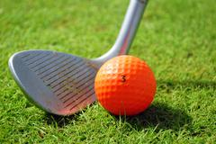 Golfclub and orange golf ball.JPG Stock Photos