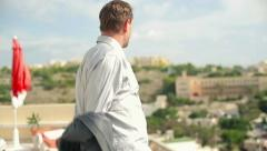 Happy businessman undressing and relaxing on terrace HD Stock Footage