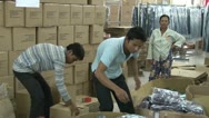 Stock Video Footage of Textile Garment Factory: Two male workers pack completed garments in boxes