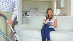 Man hoovering carpet while wife is reading on sofa Stock Footage