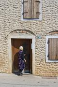 Old lady and the stone house in Galizana - stock photo