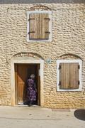 Old lady entering her stony house in Galizana Stock Photos