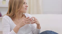 Calm woman thinking while drinking a hot drink Stock Footage