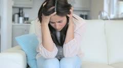 Sad woman sitting on the sofa Stock Footage