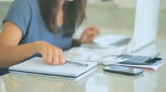 Hurried woman working on her bills - stock footage