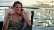 Happy woman talking on cellphone and drinking wine, crane shot HD Stock Footage
