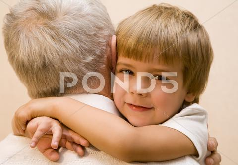 Stock photo of Little boy embrace his grandpa