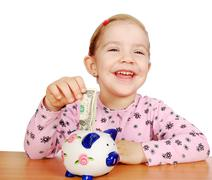 happy little girl with piggy bank.JPG - stock photo