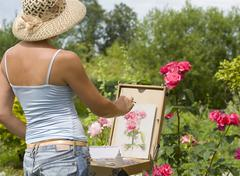 Young woman painting roses Stock Photos