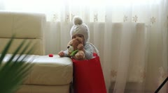 Cute baby boy and teddy bear sitting in a red gift bag, perfect present - stock footage