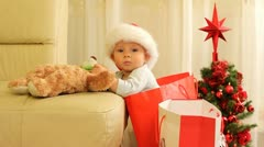 Most beautiful Chrismas present, a baby in a gift  bag holding a teddy bear - stock footage