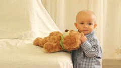 Little baby boy dancing near teddy bear toy - stock footage