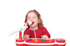 Little girl sing and play music.JPG Stock Photos
