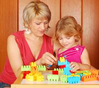 Mother and daughter play with toy brick.JPG Stock Photos