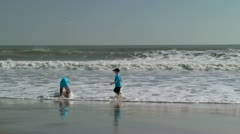 Two boys playing on beach in the ocean surf - stock footage