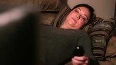 Woman laying on the couch watching tv Stock Footage