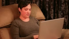 Woman sitting in a recliner while using a laptop computer - stock footage