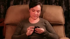 Woman texting while sitting in a recliner - stock footage