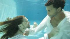 Interracial male couple interacting underwater sensually. Stock Footage