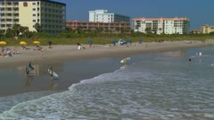 Surfers head to the ocean along Cocoa beach Stock Footage