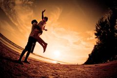 romantic scene of couples on the beach - stock photo
