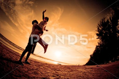 Stock photo of romantic scene of couples on the beach