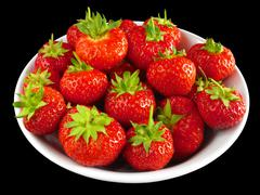 strawberries in a white bowl isolated over black. - stock photo