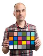 man holds an white balance card with test colors - stock photo