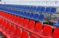 Rows of red, blue and white plastic chairs Stock Photos