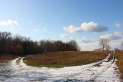 Snow dirt road in a sunny day against a blue sky - stock photo