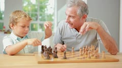 Child learning to play chess with his grandpa Stock Footage