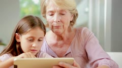 Child using tablet with her granny Stock Footage