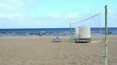 Seaside beach volleyball net blue benches and people walk Stock Footage