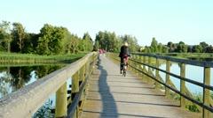 People walk go bicicle wooden lake bridge. woman enjoy view Stock Footage