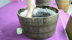 Young girl with nice legs make fresh wine from grape in the wooden barrel. Stock Footage