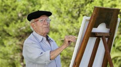 Old man painting - stock footage