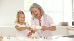 Little girl rolling out pastry with grandmother Stock Footage