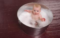 6 month old boy taking bubble bath in metal tub Stock Photos