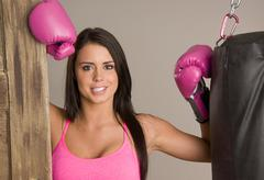 Stock Photo of pretty young female boxer wearing pink boxing gloves