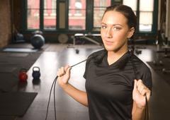 woman pauses during rope work at fitness boot camp - stock photo