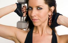 pretty athletic woman lifting silver barbells in head and shoulders pose - stock photo