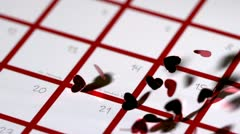 Dark red heart confetti dropping on calendar - stock footage