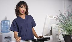 nurse breaks for a look at camera in the health care center - stock photo